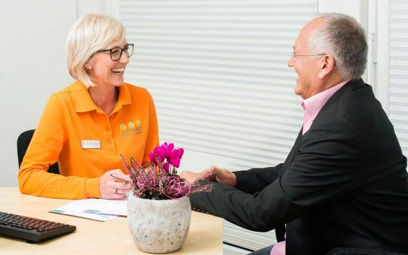Beratung in der Zahnarztpraxis - Austausch einer Mitarbeiterin mit Klaus Schmitt